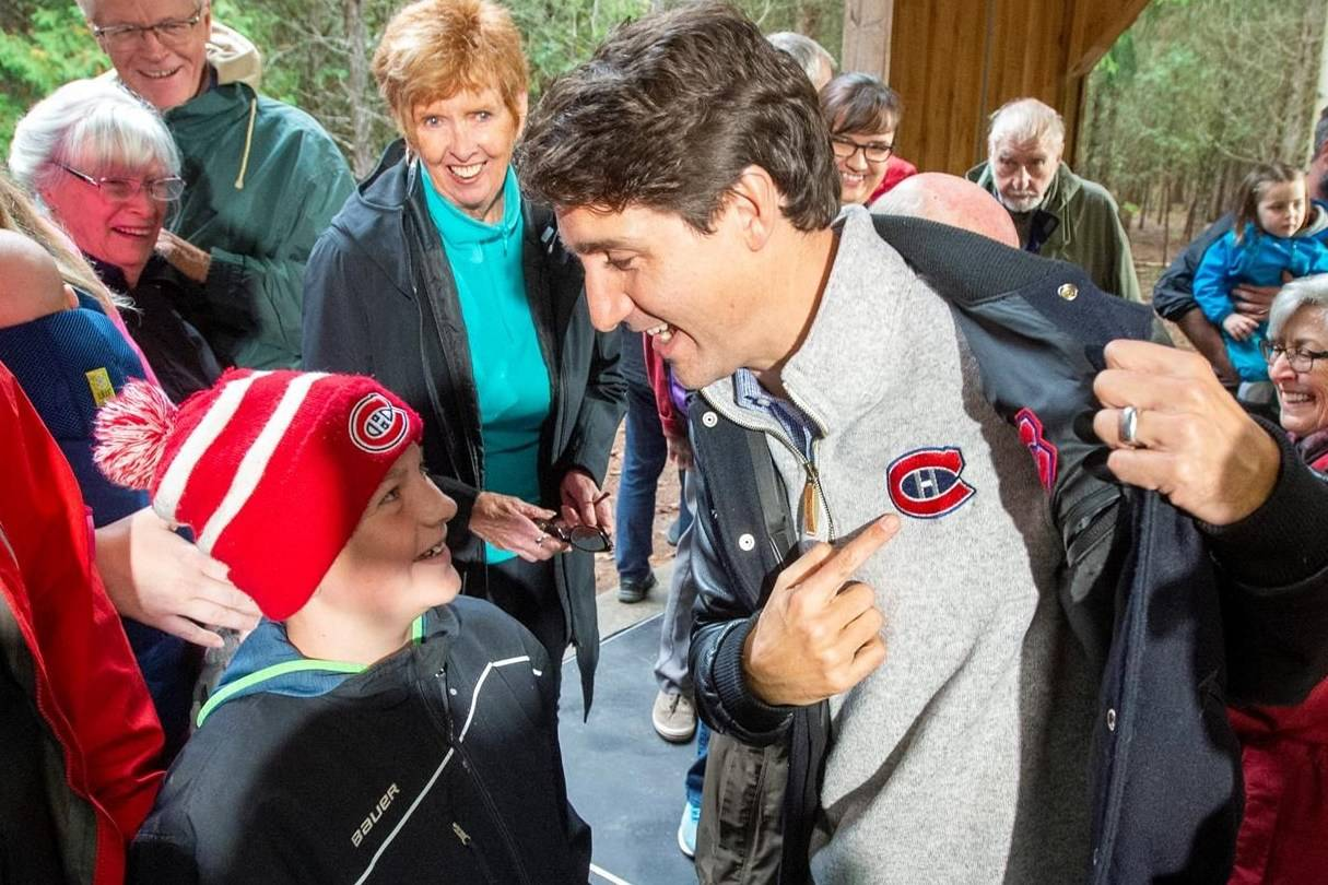 Justin Trudeau speaks with a young Montreal Canadiens fan at the Frank Conservation Area in Plainfield, Ont. on Sunday, Oct. 6, 2019. Prime Minister Trudeau says that as a lifelong Montreal Canadiens fan he's disappointed by the team's selection of Logan Mailloux in the NHL draft. THE CANADIAN PRESS/Frank Gunn